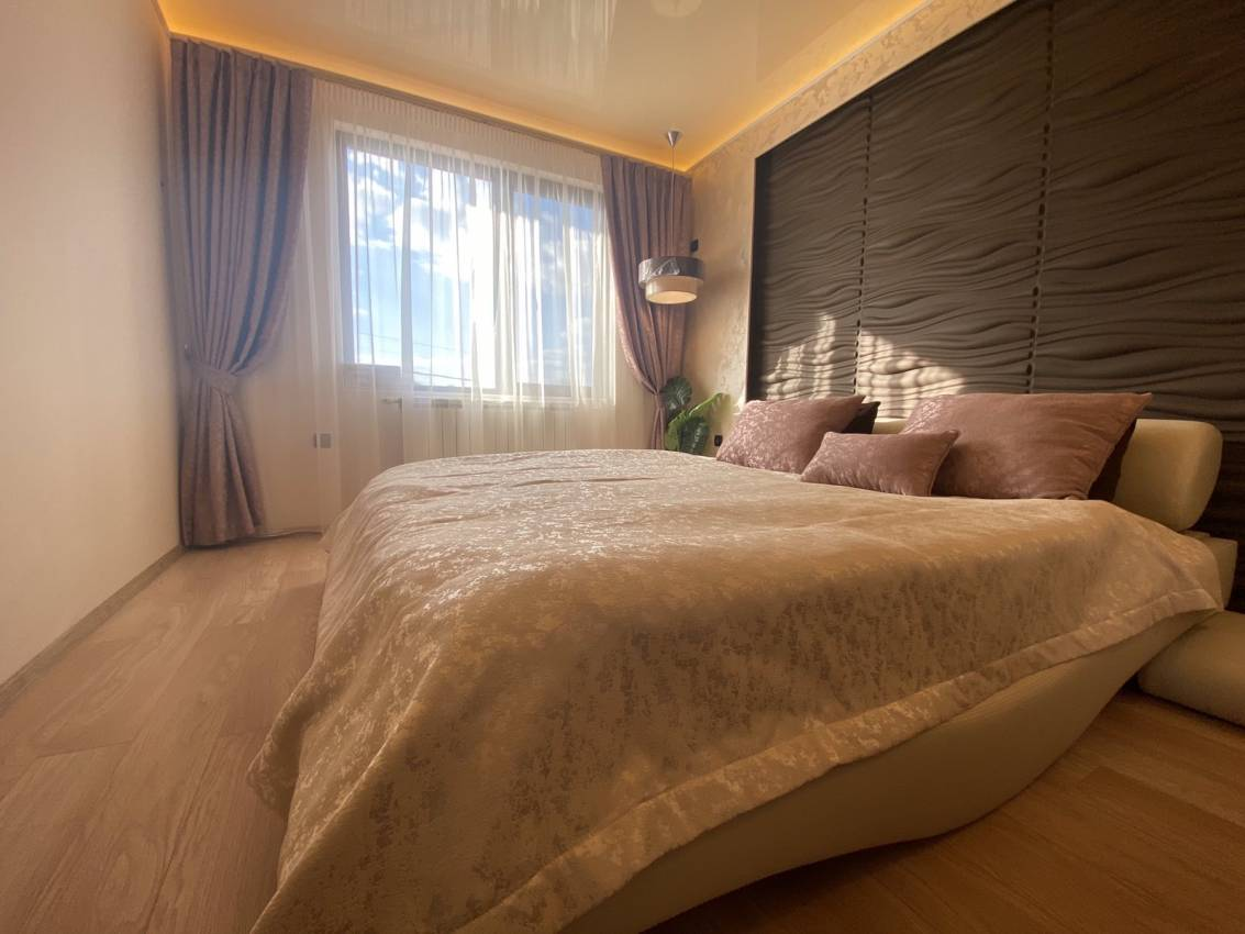 Спалня със сатенени завеси, шалте и декоративни възглавници
